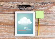 Close up of tablet pc transferring data. Business, education, objects and technology concept - close up of tablet pc transferring data, eyeglasses and stickers Royalty Free Stock Photos