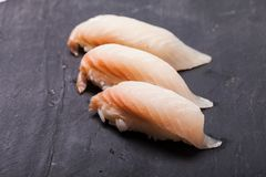 Tai nigiri sushi. Close-up of Tai nigiri sushi on a black slate background Stock Images