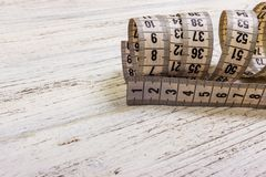 Close up tailor measuring tape on wooden table background. White measuring tape shallow dept of field Stock Photo