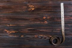 Close up tailor measuring tape on wooden table background. White measuring tape shallow dept of field Stock Images