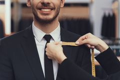 Close up. Tailor uses measuring tape to measure dimensions of customer for tailoring suit. Suit measure. New suit purchase Royalty Free Stock Image