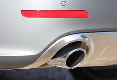 Exhaust pipe system. Close up of tailpipe on grey passenger car Royalty Free Stock Images