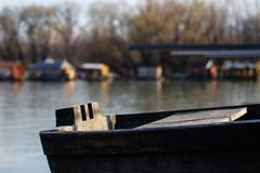 Wooden boat at river banks and winter sun. Close up take on the old river boat, Colorful houses on the river banks, Calm day on Sava river royalty free stock photos