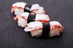 Tako nigiri sushi. Close-up of Tako nigiri sushi with cooked octopus on a black slate background Royalty Free Stock Photo