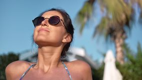 Close-up tanned face of smiling brunette woman in sunglasses enjoying sunbathing in bikini on beach
