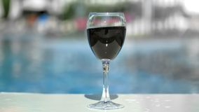 Close-up tanned female hand putting glass bocal red wine at swimming pool background slowmo