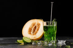 Close-up of a tarragon drink. A glass of green alcoholic cocktai. Cold herbal drink and melon on a black background. Copy space. Stock Photography