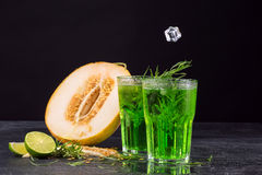 Close-up of a tarragon drink. A glass of green alcoholic lime cocktail. Cold  drink and sweet cut melon on a black background. Royalty Free Stock Photo