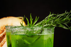 Close-up of a tarragon drink. A glass of green alcoholic lime cocktail. Cold herbal drink and sweet melon on a black background. Royalty Free Stock Photos