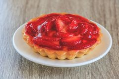 Close-up of tartlet with vanilla cream covered with slices of strawberry. stock photos