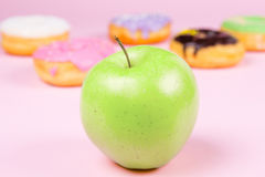 Close-up of tasty donuts and fresh green apple on pink background suggesting healthy food concept Stock Photos