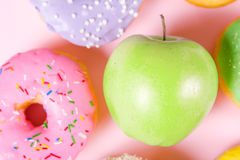 Close-up of tasty donuts and fresh green apple on pink background suggesting healthy food concept Royalty Free Stock Image