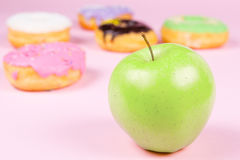 Close-up of tasty donuts and fresh green apple on pink background suggesting healthy food concept Royalty Free Stock Photo
