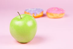 Close-up of tasty donuts and fresh green apple on pink background suggesting healthy food concept Stock Photography