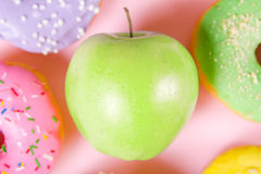 Close-up of tasty donuts and fresh green apple on pink background suggesting healthy food concept Royalty Free Stock Images