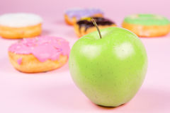 Close-up of tasty donuts and fresh green apple on pink background suggesting healthy food concept Stock Images
