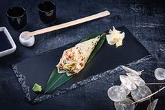 Close-up of tasty hand roll sushi in mamenori with crab and Tobico caviar served on dark stone plate with soy sauce and ginger. Copy space. Temaki, Japanese stock photography