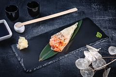 Close-up of tasty hand roll sushi in mamenori with salmon and Tobico caviar served on dark stone plate with soy sauce and ginger. Copy space. Temaki, Japanese royalty free stock photography