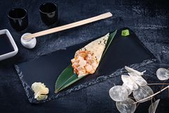 Close-up of tasty hand roll sushi in mamenori with scallop and Tobico caviar served on dark stone plate with soy sauce and ginger. Copy space. Temaki, Japanese royalty free stock photos