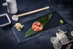 Close-up of tasty hand roll sushi with tuna and Tobico caviar served on dark stone plate with soy sauce and ginger. Copy space. Temaki, Japanese cuisine royalty free stock image