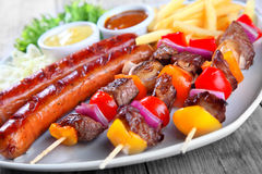 Close up Tasty Kebabs and Sausage on Plate Stock Images