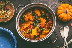 Close up of tasty pumpkin dish in cooking pot on dark rustic kitchen table background, top view. Pumpkin stew. Autumn seasonal rustic country food stock images