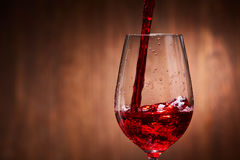 Close-up of tasty red wine pouring in the pure fragile wineglass standing against wooden background. Natural material and product. Relaxation and celebration Royalty Free Stock Photos