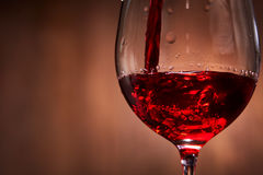 Close-up of tasty red wine pouring in the pure fragile wineglass standing against wooden background. Royalty Free Stock Image