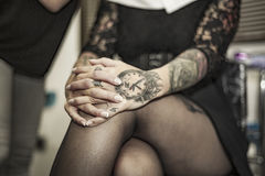 Close up tattooed hands with interlace fingers. Relax attitude Royalty Free Stock Images