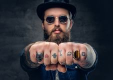 Close-up tattooed hipster`s fingers with rings. Close up tattooed hipster`s fingers with rings Royalty Free Stock Photography