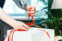 Close up of man cook ties red ribbon on white cake packaging royalty free stock image