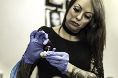 Close up tattooer hand with latex glove holding a tattoo ink nee Stock Photography
