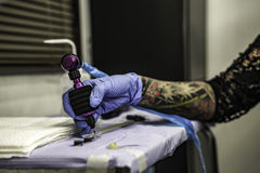 Close up tattooer hand with latex glove holding a tattoo ink nee Stock Image
