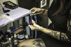 Close up tattooer hands changing tattoo machinery needle Stock Images