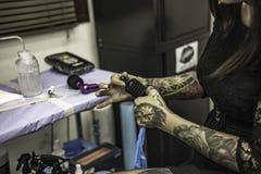 Close up tattooer hands changing tattoo machinery needle Stock Image