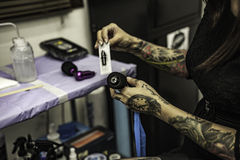 Close up tattooer hands changing tattoo machinery needle Royalty Free Stock Images
