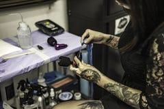 Close up tattooer hands changing tattoo machinery needle Stock Photos