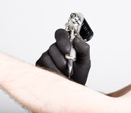Close-up of Tattooist hands in black gloves with tattoo machine Royalty Free Stock Photography