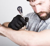 Close-up of Tattooist hands in black gloves with tattoo machine Royalty Free Stock Images