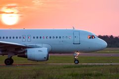 Close-up taxiing a white passenger airplane against the setting sun. Close-up taxiing a white passenger aircraft against the setting sun stock photo