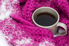 Close up of tea or coffee and winter scarf in snow Royalty Free Stock Photos