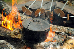 Close-up of tea pot and bread on fire. At camping Stock Photography