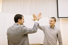 Happy student giving a high-five to a professor on a blurred background. Success concept. stock images