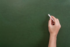 Close up of a teacher or student hand holding a chalk stick. About to write on a blank green chalkboard with copyspace Royalty Free Stock Photo