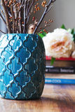 Close up of teal moroccan vase with sticks and background decor Royalty Free Stock Image