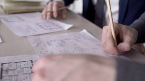 Close-up of team of engineers working on a project for building a house. In architectural office on table, papers are laid out with plans with which the stock footage