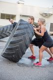 Close up of team flipping large tires outdoor Stock Photos