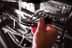 Close-Up of technician plugging patch cable in a rack mounted server stock photography