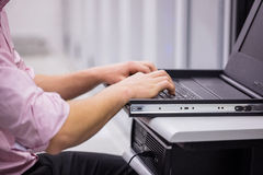 Close up of technician sitting using laptop to diagnose servers Royalty Free Stock Photography