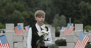 Close up of teen boy holding lily flowers while standing near grave of his father. Kid honoring his dad soldier at